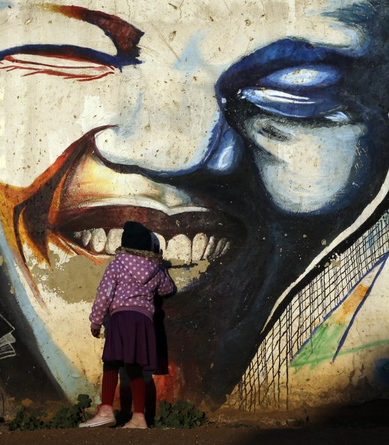 A young girl kisses a mural showing former South African president Nelson Mandela's face at Katlehong township, 35 km east of Saturday, July 18, 2015. On Mandela Day, people around the world are encouraged to spend at least 67 minutes doing something positive for their communities in honor of the 67 years that the late South African president Nelson Mandela spent fighting for social justice and a free, democratic country. (Photo by Themba Hadebe/AP Photo)