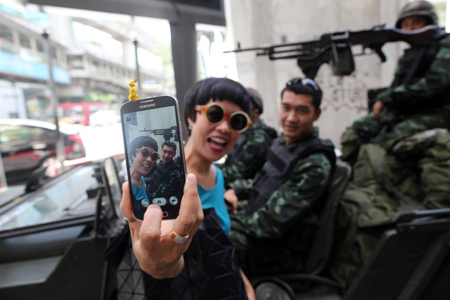 "A woman takes a ""selfie"" photograph with Royal Thai Army soldiers stationed at the Ratchaprasong intersection in central Bangkok, Thailand, on Tuesday, May 20, 2014. Thailand's army imposed martial law nationwide after months of political turmoil that brought down an elected leader and tipped the economy into a contraction. (Photo by Dario Pignatelli/Bloomberg via Getty Images)"