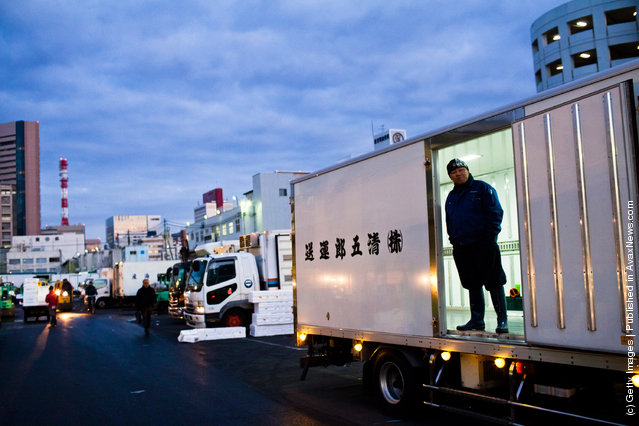A worker waits for goods to be packed into a truck at the Tsukiji fish market