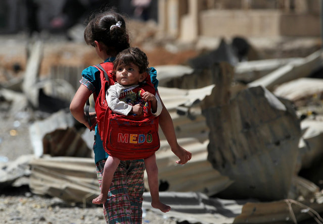 An Iraqi girl carries a baby in a backpack turned into a baby carrier as displaced Iraqis from western Mosul's al-Islah al-Zaraye neighbourhood flee their area on May 12, 2017 during a government forces' military offensive to retake the area from Islamic State (IS) group fighters. (Photo by Ahmad Al-Rubaye/AFP Photo)