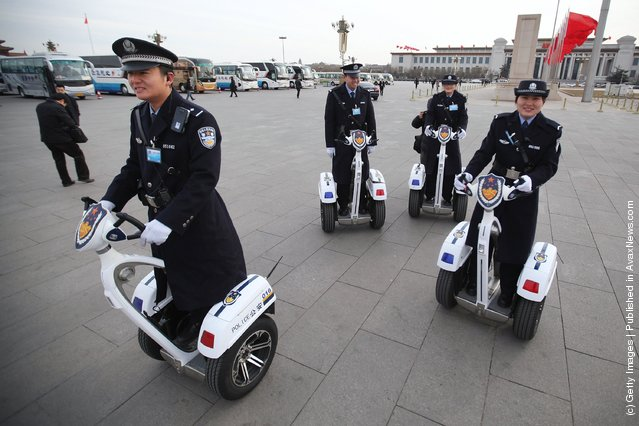 Police officers on motorized vehicles patrol at Beijing's Tiananmen Square outside The Great Hall Of The People before the second plenary meeting of the National People's Congress (NPC)
