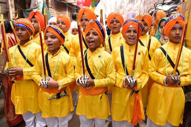 """Youth Sikh devotees hold swords as they participate in a """"Nagar Kirtan"""" (holy procession) on the eve of the 550th birth anniversary of Sikhism founder Sri Guru Nanak Dev, at the Golden Temple in Amritsar on November 11, 2019. (Photo by Narinder Nanu/AFP Photo)"""