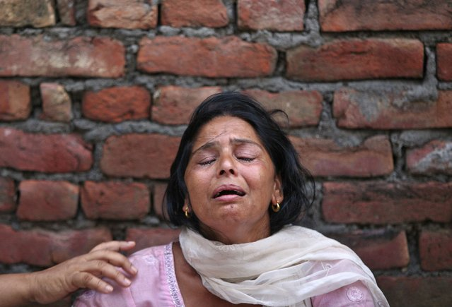Kiran Bala, wife of Amarjit Kumar, a shopkeeper who was killed in a gunfight, weeps at her residence on the outskirts of Dinanagar town in Gurdaspur district of Punjab, India, July 27, 2015. (Photo by Mukesh Gupta/Reuters)