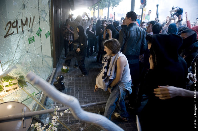 Demonstrators smash a shop window of the El Corte Ingles department store during heavy clashes with riot police during a 24-hour strike on March 29, 2012 in Barcelona, Spain