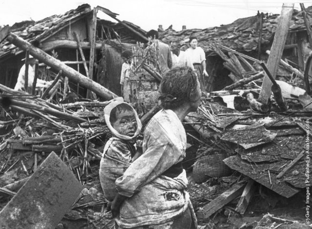 1950: An elderly woman and her grandchild wander among the debris of their wrecked home in the aftermath of an air raid by U.S. planes over Pyongyang, the Communist capital of North Korea