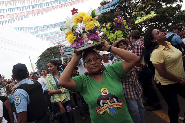 A devotee carries a figurine of Santo Domingo de Guzman on his head during celebrations honoring the patron saint in Managua, Nicaragua, August 1, 2015. (Photo by Oswaldo Rivas/Reuters)