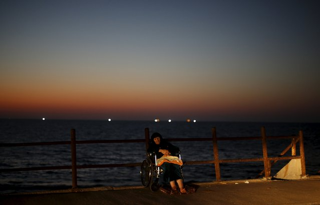 A disabled Palestinian woman sits on a beach as she flees the heat during power cut at Shatti (beach) refugee camp in Gaza City July 23, 2015. (Photo by Mohammed Salem/Reuters)