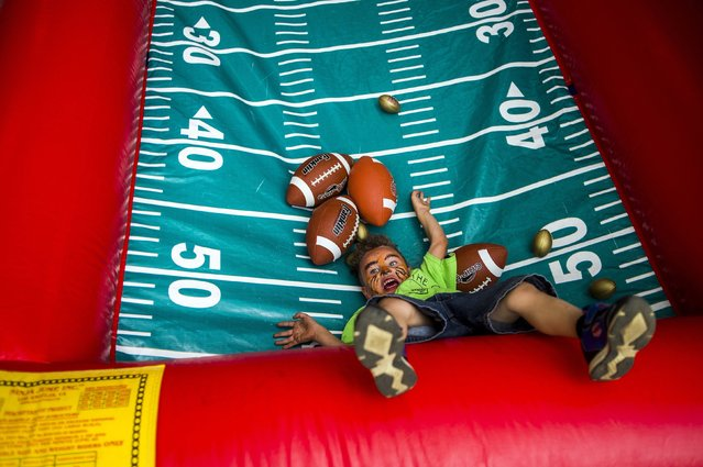 Xavier Fleming, 4, of Mt. Morris, smiles as he falls backward into a pile of footballs while reaching for them to continue playing in a large inflatable toss game as law enforcement agencies gather for Light Up the City on Thursday, June 9, 2016 at Cook Park in Flint, Mich., on the city's east side with more than 70 Flint residents to form bonds and build trust in an effort to combat crime in Flint. (Photo by Jake May/The Flint Journal-MLive.com via AP Photo)