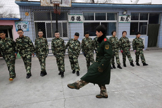 An ex-military instructor teaches students during their military-style close-order drill class at the Qide Education Center in Beijing February 19, 2014. The Qide Education Center is a military-style boot camp which offers treatment for internet addiction. (Photo by Kim Kyung-Hoon/Reuters)