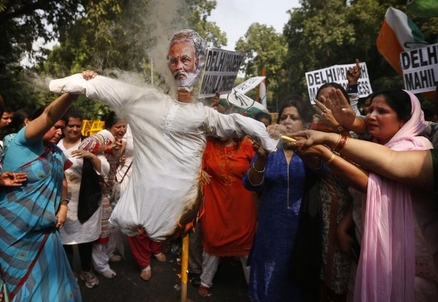 "India's opposition Congress party workers burn an effigy of Prime Minister Narendra Modi outside the office of the ruling Bharatiya Janata Party (BJP) in New Delhi, India, Tuesday, August 4, 2015. Tuesday's protest followed after the speaker of India's Parliament on Monday barred 25 opposition legislators from its sessions for the rest of the week for causing ""grave disorder"" after they created noisy scenes. (Photo by Saurabh Das/AP Photo)"