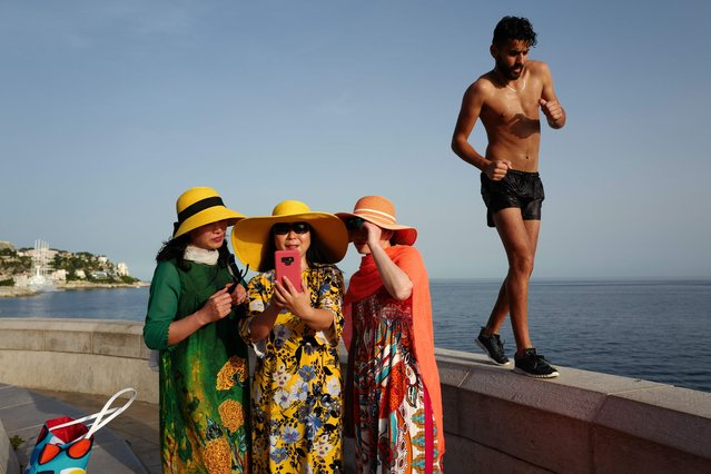 A man walks by as tourists take selfies on the French Riviera city of Nice on June 24, 2019, as temperatures soar to 33 degrees Celsius. (Photo by Valery Hache/AFP Photo)