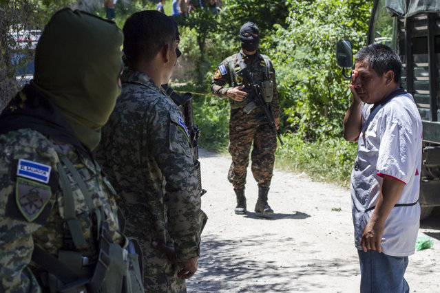 A victim's relative speaks with soldiers guarding the scene after a passenger bus was attacked in San Pedro Perulapan, El Salvador, Wednesday, August 5, 2015. Gunmen boarded the bus near the Salvadoran capital and opened fire, killing four people and wounding several others a week after a string of bus attacks brought service to a halt. (Photo by Salvador Melendez/AP Photo)