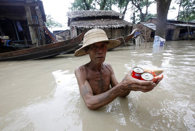 A man standing in floodwaters receives food in Nyaung Tone, in the Irrawaddy Delta, southwest of Yangon, Myanmar, Friday, August 7, 2015. Dozens have died from recent weeks of flooding and more than hundreds of thousands of people across 12 of the country's 14 states and regions have been affected, according to the U.N. Office for Coordination of Humanitarian Affairs. The floodwaters have been spreading from northern and central Myanmar to the populous Irrawaddy Delta, the country's rice bowl. (Photo by Khin Maung Win/AP Photo)