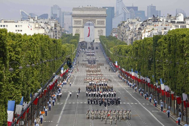 Troops march down the Champs-Elysees avenue during the traditional Bastille Day military parade in Paris July 14, 2014. In the background, the  Arc de Triomphe. (Photo by Thomas Samson/Reuters)