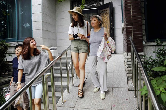 """South Korean former """"comfort woman"""" Gil Won-ok is helped by a volunteer as she heads to the weekly Wednesday protest demanding an apology and compensation from the Japanese government in Seoul, South Korea, July 22, 2015. (Photo by Kim Kyung-Hoon/Reuters)"""