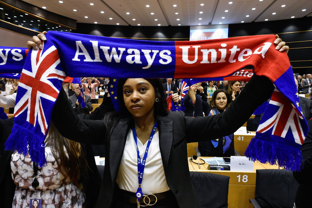 A member of the Group of the Progressive Alliance of Socialists and Democrats in the European Parliament holds a scarf depucting the European Union and the Union Jack flags during a ceremony at the Europa Building in Brussels, on January 29, 2020, as Brexit Day is to be set in stone when the European Parliament casts a vote ratifying the terms of Britain's divorce deal from the EU. (Photo by John Thys/AFP Photo)