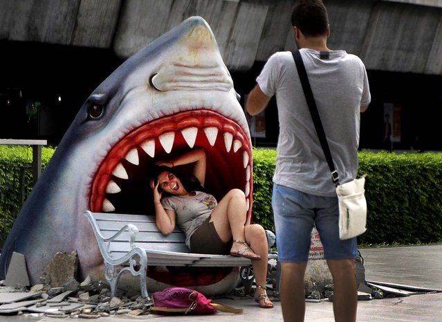 A tourist poses for a picture with a fake shark at a business district in Bangkok, Thailand on July 12, 2012
