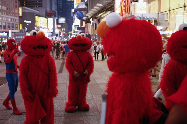Jorge, an immigrant from Mexico (C), stands amidst other people, all dressed as the Sesame Street character Elmo, while they look to make tips for photographs in Times Square in New York July 30, 2014. (Photo by Eduardo Munoz/Reuters)