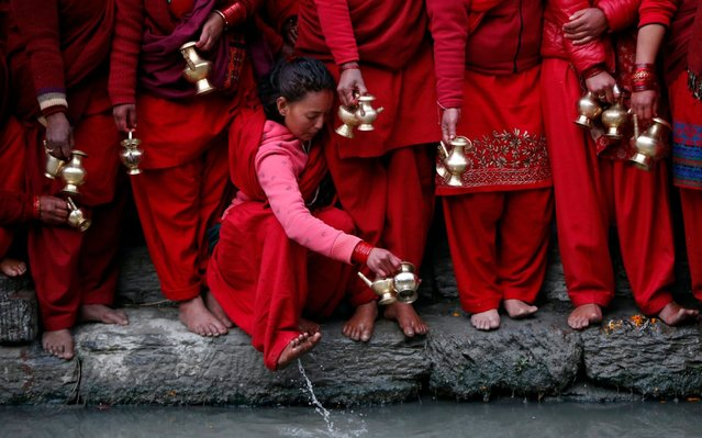 A Nepalese Hindu devotee washes her feet as she waits to collect holy water from Bagmati river to perform rituals during Madhav Narayan festival in Kathmandu, Nepal, Friday, January 24, 2020. During this month-long festival, devotees recite Holy Scriptures dedicated to Hindu goddess Swasthani and Hindu God Lord Shiva. Unmarried women pray to get a good husband while those married pray for the longevity of their husbands by observing month long fast. (Photo by Niranjan Shrestha/AP Photo)