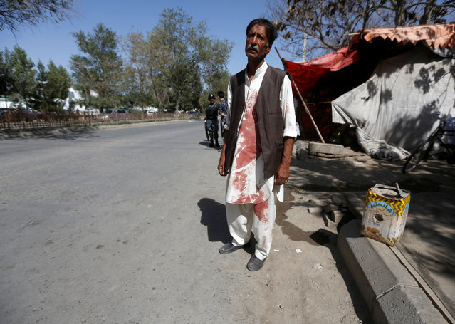 An Afghan man stands near a mosque with bloodstained clothes as he waits for his relatives who were stuck at the site of a suicide attack followed by a clash between Afghan forces and insurgents after an attack on a Shi'ite Muslim mosque in Kabul, Afghanistan on Friday, August 25, 2017. (Photo by Omar Sobhani/Reuters)