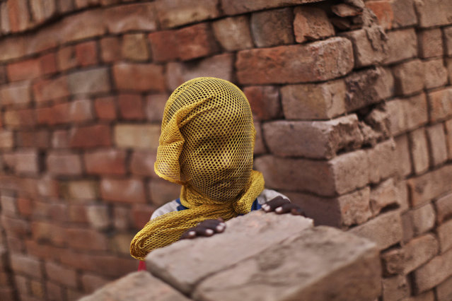 A Pakistani boy who lives near by a brick factory, covers his face with a scarf to avoid a sand storm, on the outskirts of Islamabad, Pakistan, Wednesday, June 6, 2012. (Photo by Muhammed Muheisen/AP Photo)