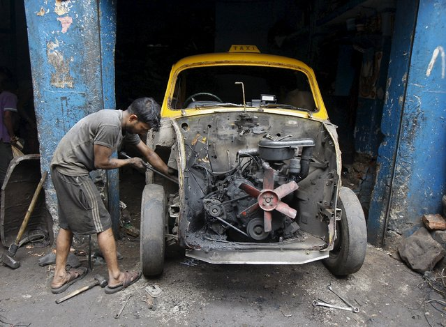 A worker dismantles an Ambassador car inside a second-hand automobile parts market in Kolkata, India, August 20, 2015. (Photo by Rupak De Chowdhuri/Reuters)