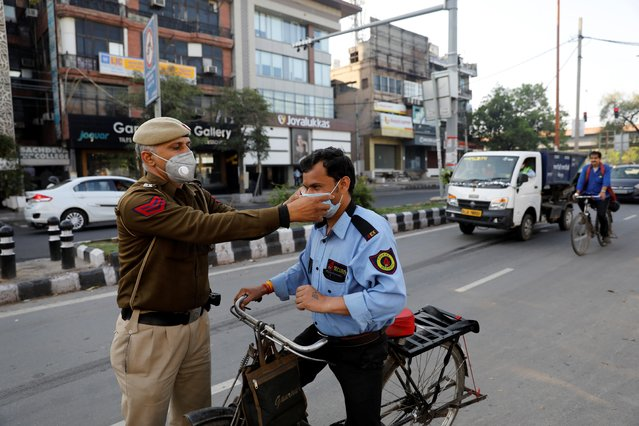 A policeman adjusts the mask of a security guard during a lockdown amid a coronavirus disease (COVID-19) outbreak in New Delhi, India, March 25, 2020. (Photo by Adnan Abidi/Reuters)