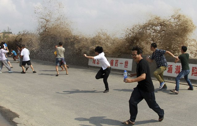 Visitors run away from a tidal bore as it surges past a barrier on the banks of Qiantang River in Hangzhou, Zhejiang province, September 20, 2013. (Photo by Reuters/China Daily)