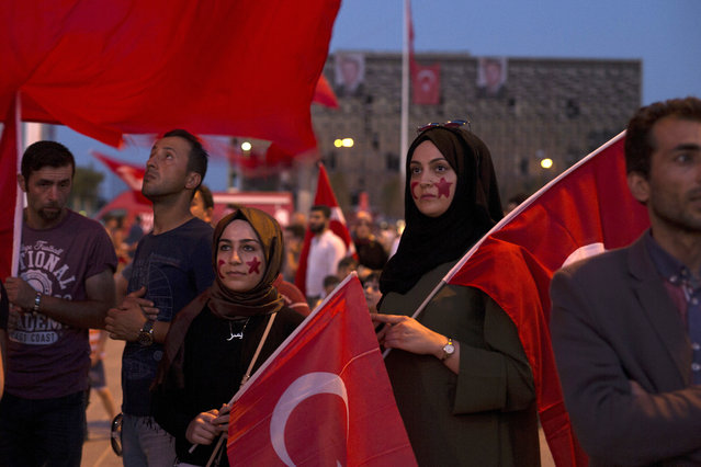 Protesters hold Turkish flags as they gather in Taksim Square in Istanbul, Sunday, July 17, 2016. The Turkish government accelerated its crackdown on alleged plotters of the failed coup against President Recep Tayyip Erdogan, with the justice minister saying Sunday that 6,000 people had been detained in the investigation, including three of the country's top generals and hundreds of soldiers. (Photo by Petros Giannakouris/AP Photo)