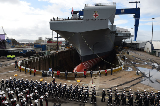 Royal Navy servicemen march past HMS Prince of Wales before a naming ceremony for the aircraft carrier at Rosyth Dockyard on September 8, 2017 in Rosyth, Scotland. HMS Prince Of Wales is the second in a new generation of aircraft carriers and will commence sea trials in 2019. (Photo by Jeff J. Mitchell/Getty Images)