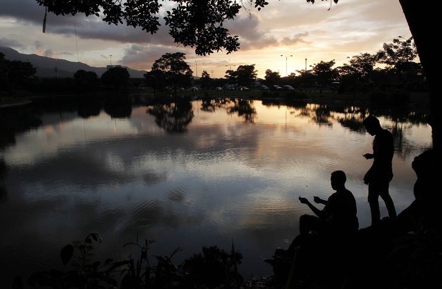Men fish in a lake at Peace park in San Jose August 5, 2014. (Photo by Juan Carlos Ulate/Reuters)