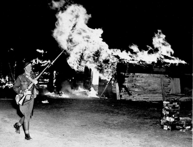 A federal soldier passes by burning shacks that fleeing Bonus March veterans abandoned, at Camp Marks, on the Anacostia Flats in Washington, D.C., July 29, 1932. This was the fourth veterans' camp to be burned. (Photo by AP Photo)