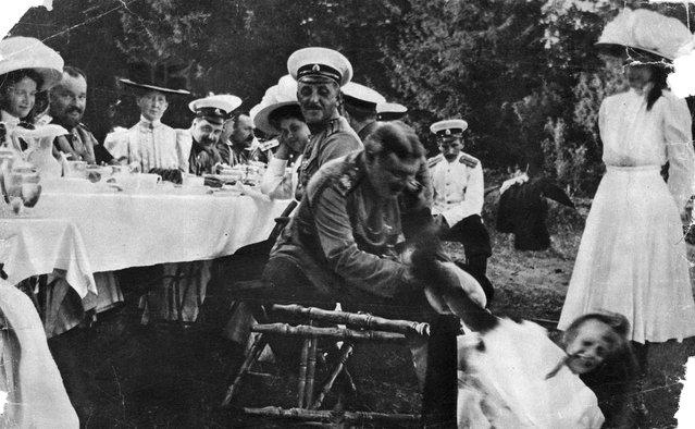 Outdoor family dinner, circa 1910.