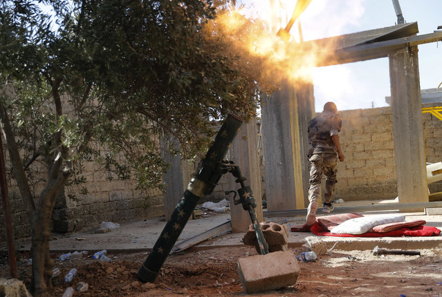 """In this July 27, 2017 file photo, a U.S.-backed Syrian Democratic Forces fighter, runs as he fires mortars at Islamic State group militant, in Raqqa, northeast Syria. The Syrian Democratic Forces said in a statement Wednesday, September 20, 2017, that the battle for the Islamic State group's de-facto capital, Raqqa, has reached its """"final stages"""" with the opening of a new front. (Photo by Hussein Malla/AP Photo)"""