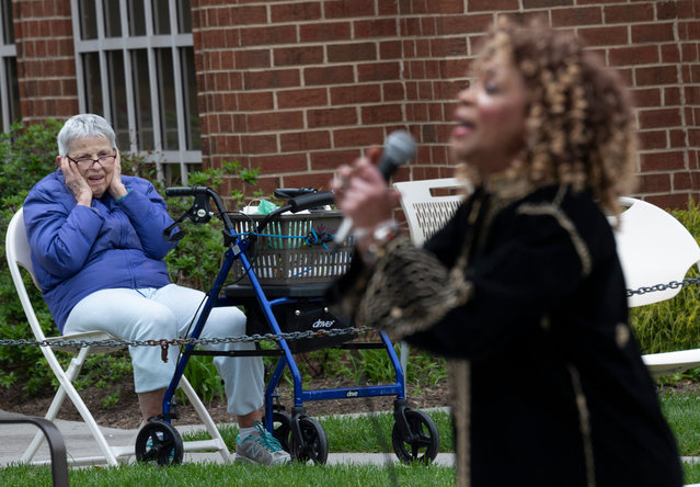"A resident of the Goodwin House senior living community, looks on as the DC area motown band ""The Tribe"" plays a social distance concert in their parking lot in Arlington, Virginia, during the coronavirus pandemic on April 14, 2020. (Photo by Andrew Caballero-Reynolds/AFP Photo)"