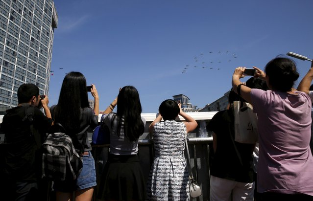 """People take pictures of military helicopters forming the number """"70"""" above buildings during the military parade to mark the 70th anniversary of the end of World War Two, in Beijing, China, September 3, 2015. (Photo by Kim Kyung-Hoon/Reuters)"""