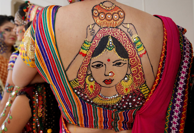 A tattoo sketched on the back of a woman is pictured in preparations for Garba, a traditional folk dance, ahead of Navratri, a festival of nine days when devotees worship Hindu goddess Durga, in Ahmedabad, India, September 20, 2017. (Photo by Amit Dave/Reuters)