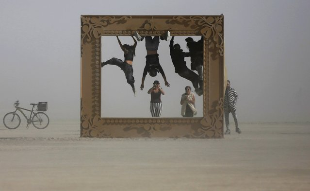 "Participants climb the art installation ""Got Framed"" during the Burning Man 2015 ""Carnival of Mirrors"" arts and music festival in the Black Rock Desert of Nevada, September 4, 2015. (Photo by Jim Urquhart/Reuters)"