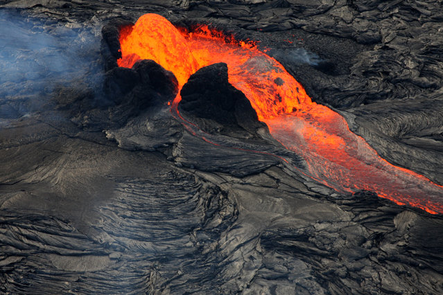 A  fountain of lava erupts from Hawaii's Kilauea volcano's  Tuesday, July 8, 2008. In the latest activity fountains of red-hot lava spew up to 30 feet high,  but the flow into the sea has once again slowed to a trickle according to the Hawaiian Volcano Observatory. (Photo by Tim Wright/AP Photo)