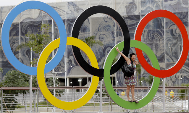 An Olympic volunteer stands on the Olympic rings as she poses for a picture prior to the Summer Olympics in Rio de Janeiro, Brazil, Wednesday, August 3, 2016. The Games opening ceremony is on Friday. (Photo by Natacha Pisarenko/AP Photo)