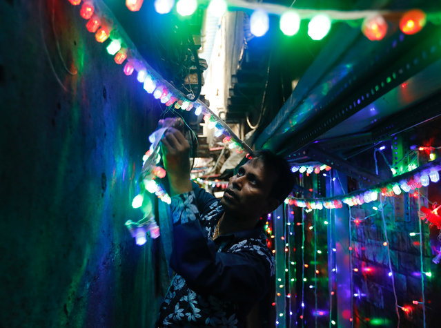 A man puts lights in an alley the eve of the Hindu festival of Diwali in a slum in Mumbai, October 18, 2017. (Photo by Danish Siddiqui/Reuters)