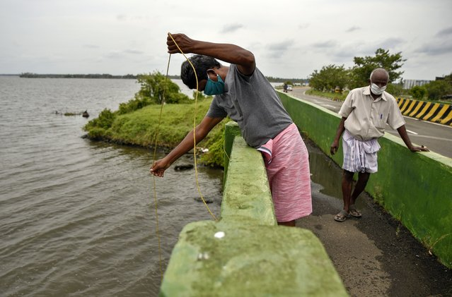 Indians wearing face masks engage in fishing during lockdown to curb the spread of coronavirus in Kochi, Kerala, India, Saturday, May 16, 2020. Prime Minister Narendra Modi's government is due to announce a decision this weekend on whether to extend the 54-day-old lockdown. (Photo by R S Iyer/AP Photo)