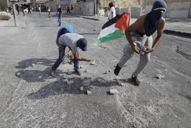 Palestinian youths collect stones to throw towards Israeli police during clashes in the east Jerusalem neighbourhood of Issawiya, September 13, 2015, after Israeli police raided the plaza outside Jerusalem's al-Aqsa mosque on Sunday in what they said was a bid to head off Palestinian attempts to disrupt visits by Jews and foreign tourists on the eve of the Jewish New Year. (Photo by Ammar Awad/Reuters)