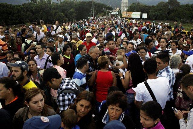 People cross over the Simon Bolivar international bridge to Colombia from San Antonio del Tachira, Venezuela, August 13, 2016. (Photo by Carlos Eduardo Ramirez/Reuters)