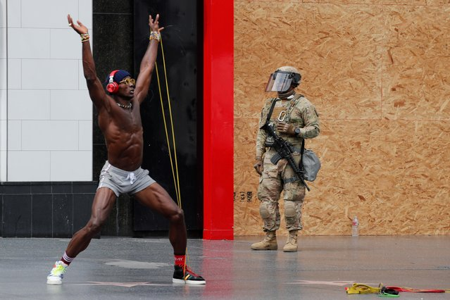 A National Guard member mounts guard as a man exercises during a rally against George Floyd death in Minneapolis police custody, in Los Angeles, California, U.S., June 2, 2020. (Photo by Mike Blake/Reuters)