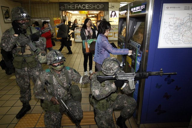 A woman uses a ticket vending machine as South Korean soldiers take part in an anti-terror and security drill at a subway station in Seoul October 25, 2012. (Photo by Kim Hong-Ji/Reuters)
