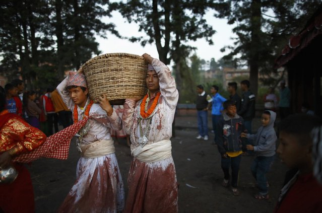 """Priests circle around the temple carrying offerings during the sacrificial ceremony held to mark the """"Dashain"""", Hinduism's biggest religious festival in Bhaktapur October 3, 2014. (Photo by Navesh Chitrakar/Reuters)"""