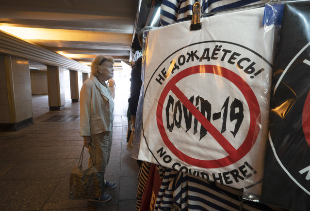 """A woman looks at souvenirs in a souvenir stall in an underpass, with a T-shirt reading """"That's not gonna happen!"""" in the foreground, amid the ongoing COVID-19 pandemic in St. Petersburg, Russia, Wednesday, June 10, 2020. (Photo by Dmitri Lovetsky/AP Photo)"""