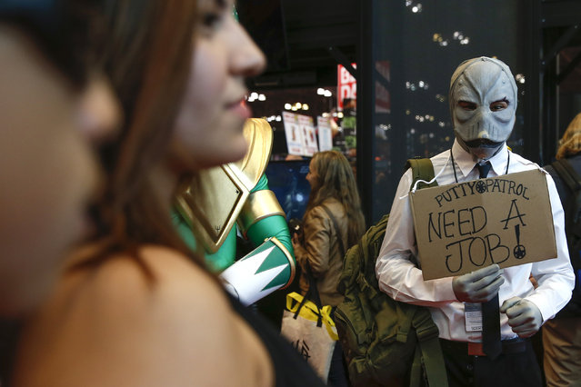 A costumed attendee holds a sign at New York's Comic-Con convention, October 9, 2014. (Photo by Shannon Stapleton/Reuters)