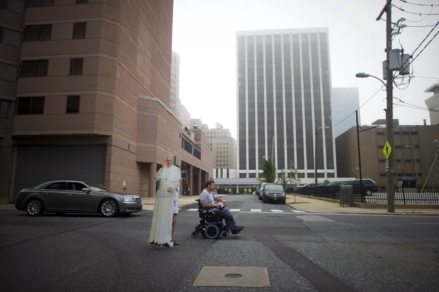 Christa Scalies (L), behind a cardboard cut-out of Pope Francis, and Paul Tanner, the creators of Pop-Up Pope, make their way along a street in Wilmington, Delaware, September 19, 2015. (Photo by Mark Makela/Reuters)